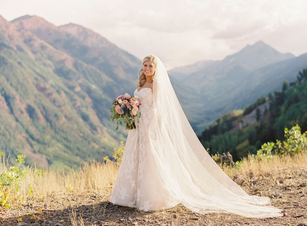 bride on top of buttermilk mountain aspen champagne lace sweetheart dress cathedral veil peach and coral bouquet september fall wedding aspen on top of mountain with expansive mountain and valley views in background